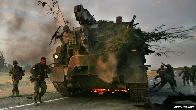 Georgian soldiers escape their burning armoured vehicle on the road during the conflict with Russia in 2008