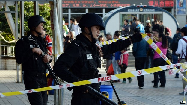 Chinese police stand guard at the scene of an attack at the main train station in Kunming, Yunnan province, China, 2 March 2014