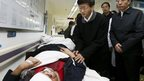 In this photo provided by China's Xinhua News Agency, China's politburo member Meng Jianzhu, second left, visits the wounded who was injured in a knife attack, at No. 1 People's Hospital in Kunming, capital of southwest China's Yunnan Province, Sunday, 2 March 2014