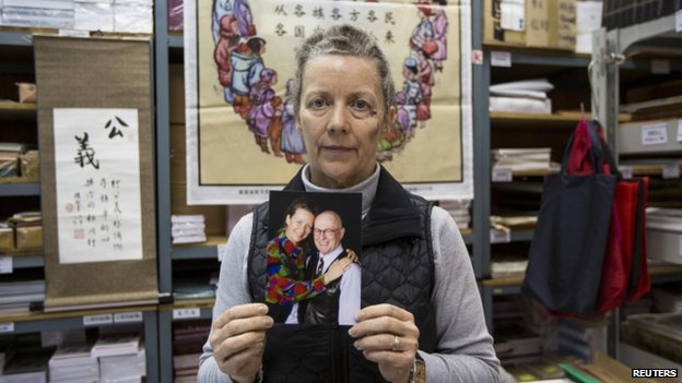 Karen Short, wife of Australian missionary John Short, poses with a photo of her husband inside the Christian Book Room in Hong Kong 20 February 2014