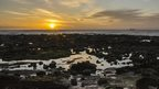 The sun glows over the sea and rock pools.