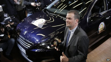 Peugeot's Maxime Picat poses with his trophy after the Peugeot 308 was elected car of the year