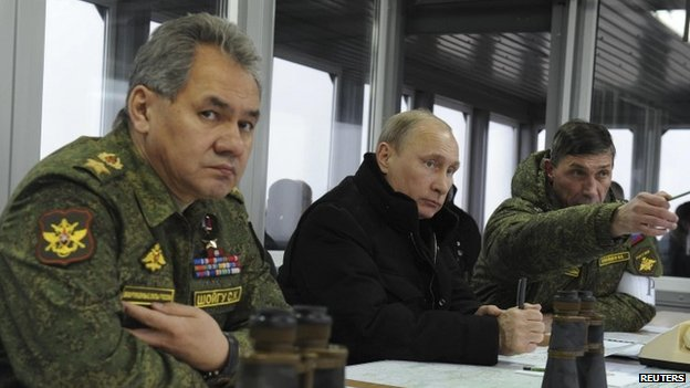 Russia's President Vladimir Putin (c), Defence Minister Sergei Shoigu (left) and head of the Russian army's main department of combat preparation Ivan Buvaltsev watch military exercises at the Kirillovsky firing ground in the Leningrad region