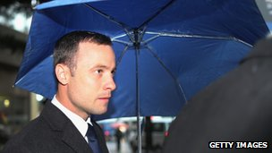 Oscar Pistorius shelters from the rain as he makes his way to North Gauteng High Court for the second day of his trial