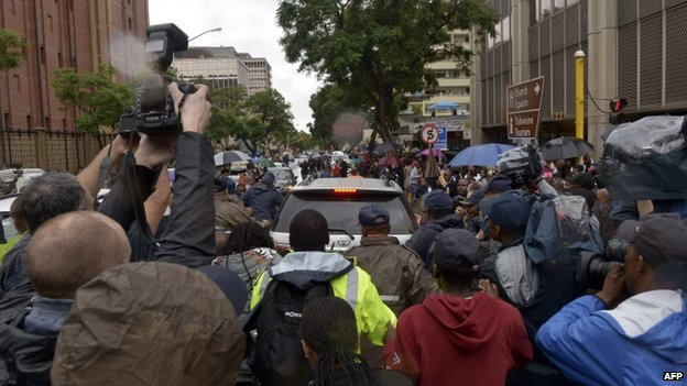 Members of the media and the public surround the vehicle of South African Paralympian star Oscar Pistorius as he leaves court on 3 March 2014
