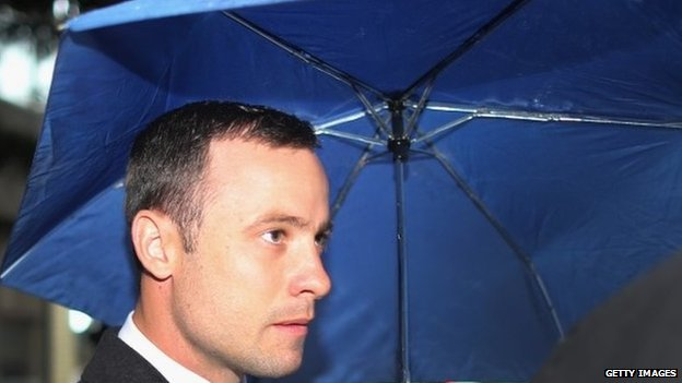 Oscar Pistorius shelters from the rain as he makes his way to North Gauteng High Court for the second day of his trial on 4 March 2014