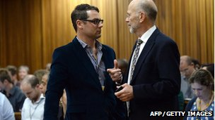 Carl Pistorius and his uncle Arnold Pistorius speak during a break in proceedings as they attend the second day of the trial