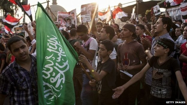 Supporter of ousted Egyptian President Mohammed Morsi holds up a Hamas flag in Cairo (12 August 2013)