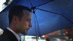 Oscar Pistorius shelters from the rain
