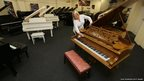 Auctioneer Karen Fairweather dusts a Bechstein piano at a showroom in Manchester