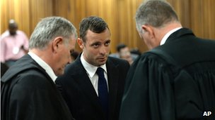 Oscar Pistorius, centre, talks with his defence lawyers Barry Roux, left, and Kenny Oldwadge, right