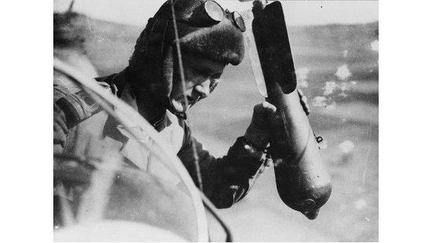 British Pilot photographed in mid-air dropping a bomb over the side of an airship control car.