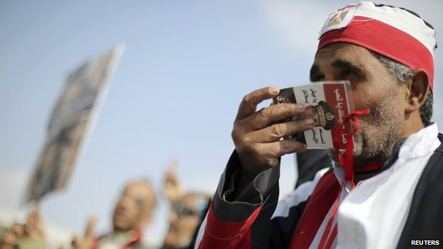 A supporter of Abdul Fattah al-Sisi kisses a photo of him at a demonstration outside the trial of ousted President Mohammed Morsi in Cairo (27 February 2014)
