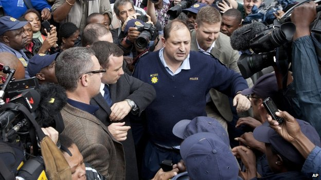 Oscar Pistorius, (centre left), leave the high court amid a scrum after the second day of his trial in Pretoria, South Africa - 4 March 2014