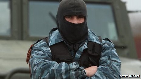 A masked pro-Russian militant stands with his arms crossed in front of a truck in Crimea on 4 March.