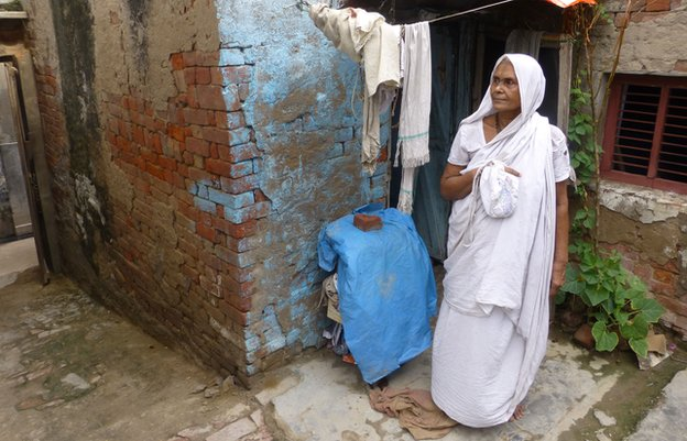 Shakti Dasi outside her small brick shack in Vrindavan