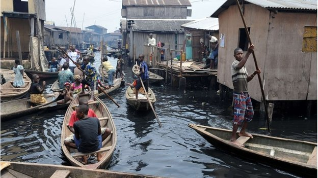 People navigate through the waterways of the Makoko slum in Lagos, Nigeria on 30 August 2012
