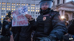 "Russian policeman detains an activist as he holds a poster reading ""Hands off Ukraine!"" during a protest rally, in front of the Defence Ministry in Moscow on 4 March 2014."