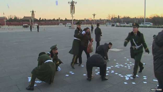 A video grab shows a protester being restrained, as paramilitary officers pick up leaflets during a protest in Tiananmen Square in Beijing, 5 March 2014