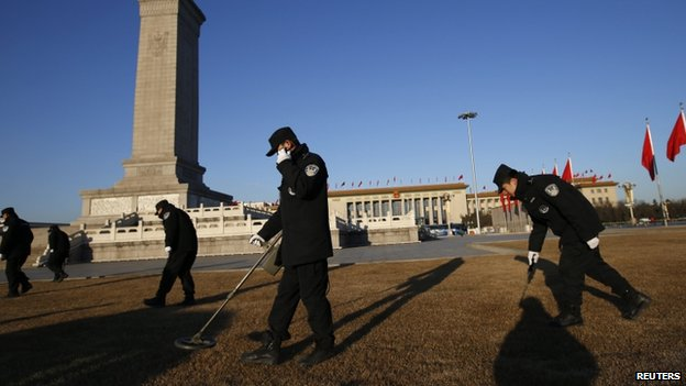 Police use metal detectors outside the Great Hall of the People at Tiananmen Square during the opening session of the National People's Congress (NPC) in Beijing, 5 March 2014