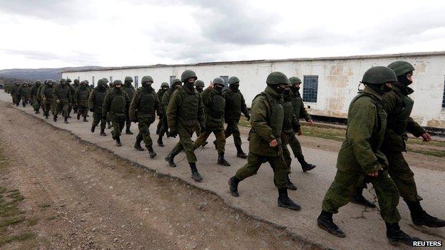 Uniformed men, believed to be Russian servicemen, march outside a Ukrainian military base near the Crimean capital Simferopol on 5 March 2014