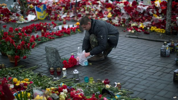 Man lights a candle at a memorial for the protesters who died in clashes with police in Kiev, on 5 March 2014