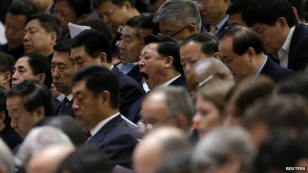 A delegate yawns as China's Premier Li Keqiang delivers the government work report during the opening ceremony of the National People's Congress at the Great Hall of the People in Beijing, 5 March 2014