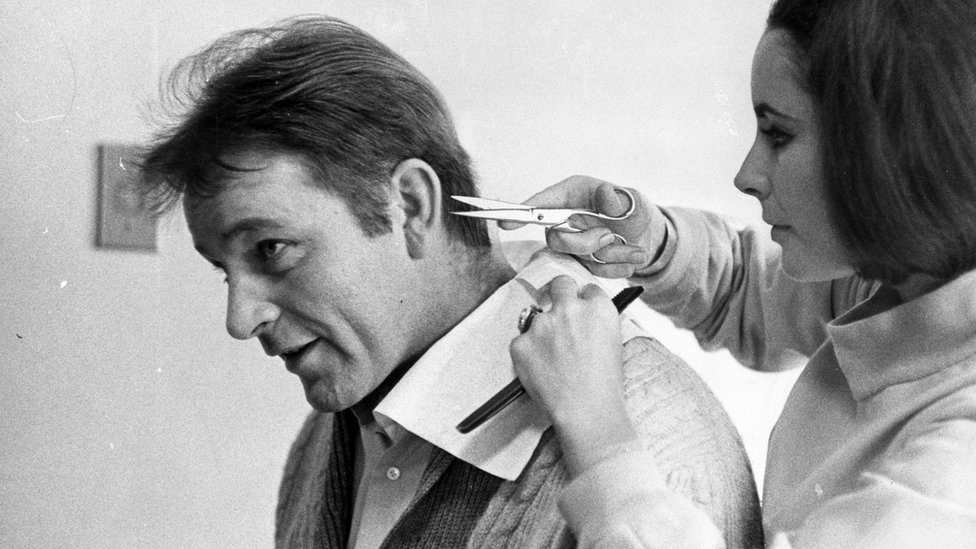 Elizabeth Taylor gives her future husband Richard Burton (1925-1984) a cursory haircut, 6 March 1964