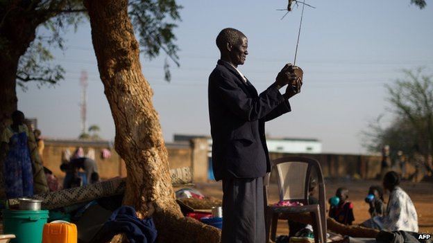 A displaced South Sudanese man tunes his radio in the grounds of St Theresa's cathedral in Juba, on 13 January 2014