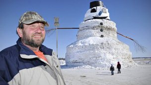Greg Novak stands next to the giant 50-foot snowman he's created in Minnesota.