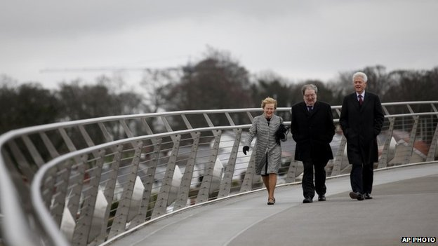 "Former US President Bill Clinton walks with former Social Democratic Labour Party leader John Hume and Hume""s wife Pat across the Peace Bridge, in Londonderry"