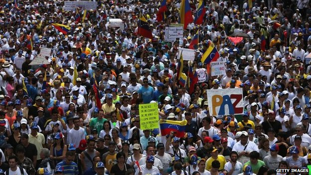 A protester carries a sign reading Peace as thousands of protesters march in an anti-government demonstration on 2 March, 2014, in Caracas