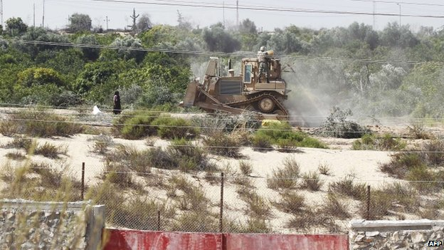 A picture taken from the southern Gaza Strip shows an Egyptian soldier standing on a bulldozer used to flatten fields near the border between Egypt and the Palestinian territory (September 2013)