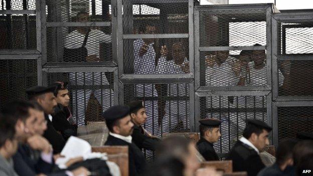 Al-Jazeera journalist Peter Greste (c) and his colleagues inside the defendants cage