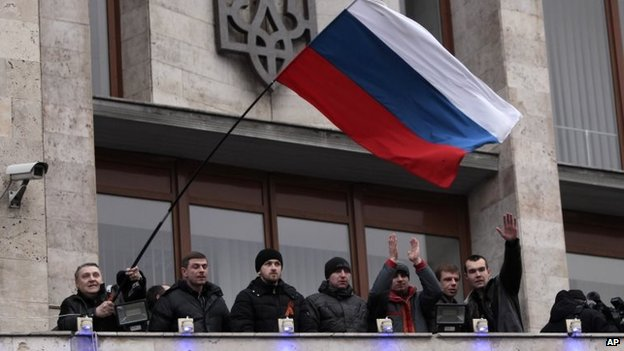 Demonstrators holding a Russian flag, with the Ukrainian emblem in the background, stand on the balcony of the regional administrative building after storming it in Donetsk