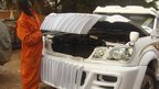 Godfrey Namunye opening the bonnet of a car at his workshop in Kampala, Uganda
