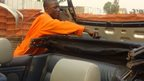Godfrey Namunye working on a car at his workshop in Kampala, Uganda