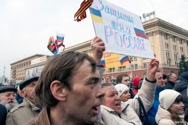 "A woman holds up a banner saying ""Protect me Russia"" at a protest in Kharkiv (5 March 2014)"
