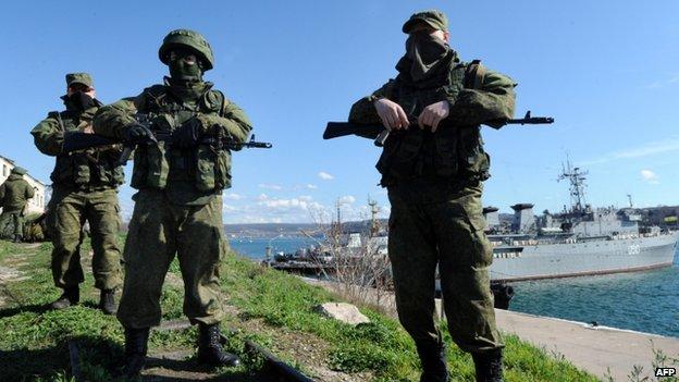 Armed men - believed to be Russian troops - patrol near the Ukrainian navy ship Slavutych in Sevastopol. Photo: 5 March 2014