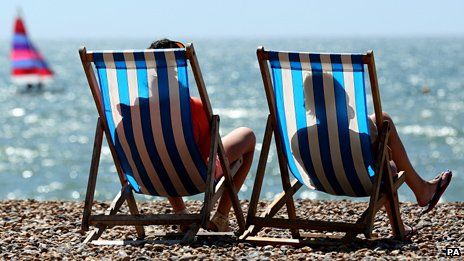 Sunbathers in deck chairs on Brighton beach in August 2013