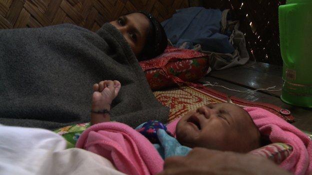Rohingya mother Kurshidaka and her baby girl. Kurshidaka badly needs treatment for her infected wound from a caesarean section