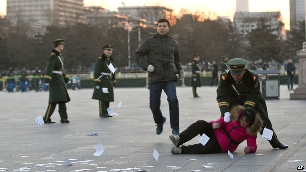 A petitioner is pushed on the ground by a paramilitary policeman after she ran into a cordoned off area near a national flag pole on Tiananmen Square and threw up flyers to protest her case of injustice during a national flag raising ceremony early in the morning before the opening session of the annual National People's Congress at the nearby Great Hall of the People in Beijing, China, 5 March 2014