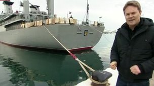 Christian Fraser stands on the dock with the Ukrainian ship Slavutich in the background