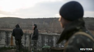 Three soldiers standing next to a wall topped with barbed wire