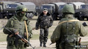 A Ukrainian soldier approaches two masked soldiers, believed to be Russian