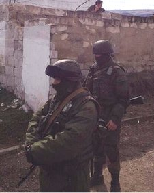 Ukrainian marine (behind a wall) peers at Russian troops outside their Perevalnoye base in Crimea