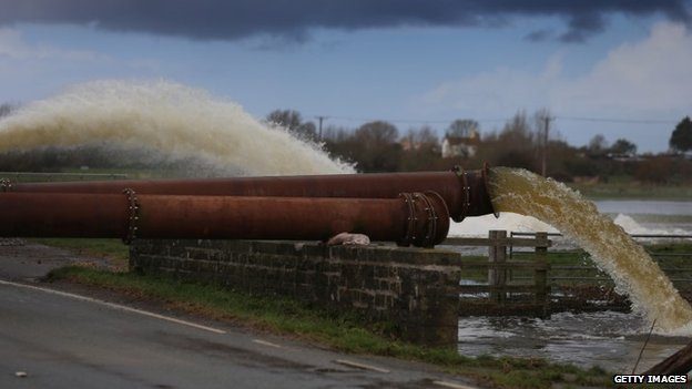 Environment Agency pipes pump flood water surrounding fields near Burrowbridge