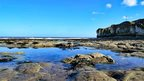 A view of rock pools and the sea. To the right are cliff faces and headland. The sky is clear blue apart from a couple of small white clouds.