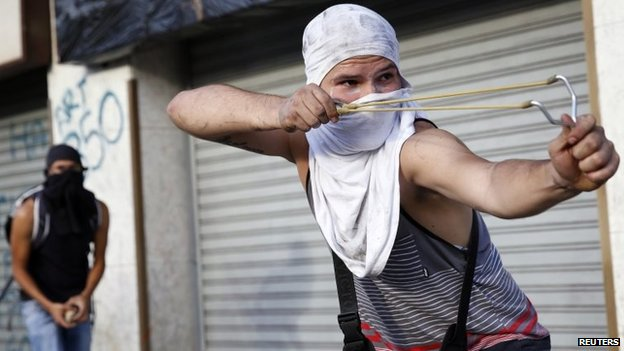 An anti-government protester uses a slingshot to shoot stones during a protest against Nicolas Maduro's government in Caracas on 3 March, 2014
