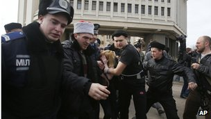 Police and Cossacks detain a woman protesting against developments in Crimea in front of the regional parliament building in Simferopol